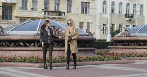 Blonde and brunette fashion women meet each other in the city center. Two girls are talking and laughing walking across the street stock video