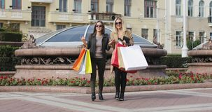 Blonde and brunette fashion women meet each other in the city center after shopping. Two girls are carrying colorful bags talking and laughing on the street stock video footage
