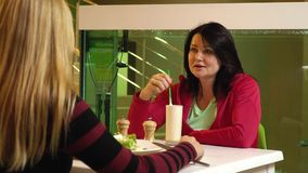 Two women sit near the aquarium in a cafe and chat, slow motion. Blonde and brunette in a fitness club cafe eat healthy food stock video