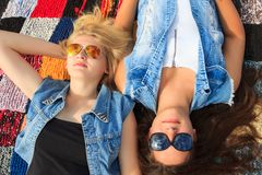 Blonde and brunette friends lying also looking up Royalty Free Stock Photography