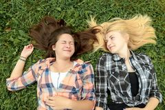 Blonde and brunette friends lying on grass Stock Photos