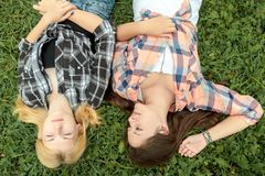 Blonde and brunette friends relaxing on grass Stock Image