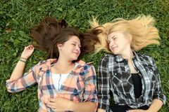 Blonde and brunette friends resting on grass Stock Photo