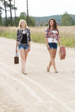 Blonde and brunette friends walking on road Royalty Free Stock Photography