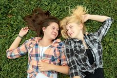 Blonde and brunette girl having rest on grass Stock Photography