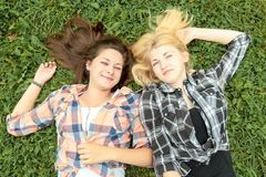 Blonde and brunette girl relaxing on grass Royalty Free Stock Images