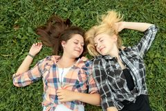 Blonde and brunette girl resting on grass Royalty Free Stock Image