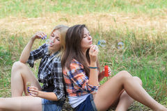 Blonde and brunette girls blowing soap bubbles in farm field Stock Photography