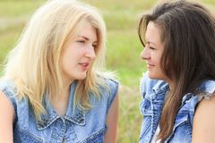 Blonde and brunette girls looking at each other Stock Images