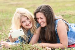 Blonde and brunette girls making selfie with phone Stock Photos