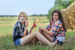 Blonde and brunette girls making soap bubbles in ranch field Royalty Free Stock Photos