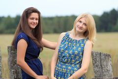 Blonde and brunette girls near wood country fence Stock Images