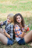 Blonde and brunette girls playing with iridescent soap bubbles Royalty Free Stock Photo
