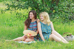 Blonde and brunette girls sitting with organic farming harvest Stock Photos