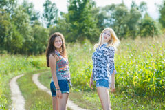 Blonde and brunette girls standing on country road Royalty Free Stock Images