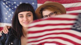 Blonde and brunette hipster girls hold a flag. Two patriotic and nationalist conservative women giggle and laugh in the camera, wear hipster outfits red checked stock video