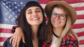 Blonde and brunette hipster girls hold a flag