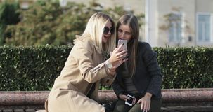 Blonde and brunette looking at mobile phone screen smiling and laughing sitting on bench in park. Girls friends spending time together outdoor stock footage