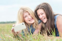 Blonde and brunette making selfie with phone Stock Photo