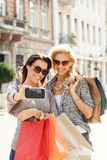 Blonde and brunette in shopping taking a selfie Stock Photography