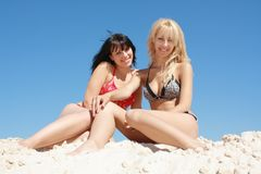 Blonde and brunette sits on the beach Royalty Free Stock Photography