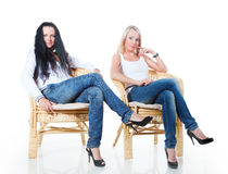 Blonde and brunette are sitting in an armchair Stock Photos