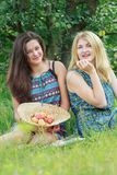 Blonde and brunette sitting on grass in farm summer arboretum Stock Photos