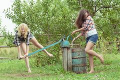 Blonde and brunette soaking each other with water Royalty Free Stock Photo