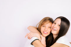 Blonde and brunette teen girls cuddling and laughi Royalty Free Stock Photography