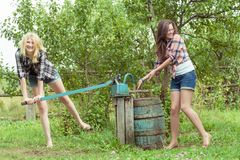 Blonde and brunette throwing water over each other Royalty Free Stock Photo