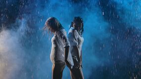 A blonde and a brunette in wet white shirts are dancing passionately in the rain. Silhouettes of wet female bodies in