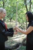 Blonde and brunette in wood with samurai sabre Royalty Free Stock Photos