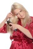 Blonde brushing her hairs Stock Image