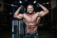 Brutal strong bodybuilder athletic men pumping up muscles with d. Blonde brutal sexy strong bodybuilder athletic fitness man pumping up abs muscles workout Royalty Free Stock Image