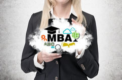Blonde business lady is holding a cloud with business education icons. A concept of the MBA degree stock photography