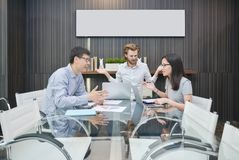 Blonde business man does not understand native language in meeti. Blonde business men does not understand native language in meeting room Royalty Free Stock Image