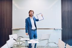 Blonde business man holding blank paper on blank glass board.  Royalty Free Stock Photos