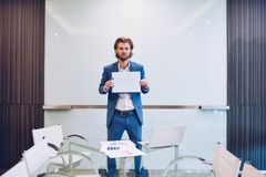 Blonde business man holding blank paper on blank glass board.  Royalty Free Stock Images
