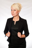 Blonde business woman in a black suit. A blonde Caucasian woman in a black business suit looking toward the camera with confidence Royalty Free Stock Photography