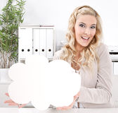 Blonde business woman with a blank sign in his hand at workplace. Woman with a blank sign Royalty Free Stock Photos