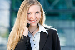 Blonde business woman on mobile phone. Blonde business woman in front of office building talking on cell mobile phone Royalty Free Stock Images