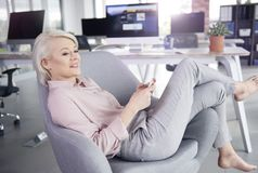 Blonde business woman in the office. Barefoot businesswoman lying on armchair with mobilephone Stock Photos