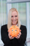 Blonde business woman with a piggy bank. Smiling blonde business woman holding a piggy bank - selective focus Stock Image