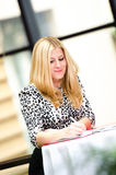 Blonde business woman standing and writing Stock Photos