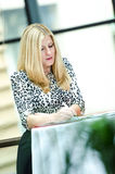 Blonde business woman standing and writing Stock Photography