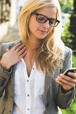 Blonde business woman using cell phone Stock Images
