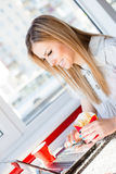 Blonde business young woman holding fries printing on a laptop happy smiling on light window background Royalty Free Stock Image