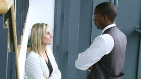 Blonde businesswoman and AfroAmerican businessman talking in workplace footage. In high definition stock footage