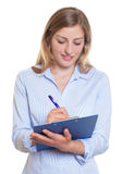 Blonde businesswoman with clipboard writing noted Stock Images