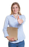 Blonde businesswoman with file showing thumb up Stock Image